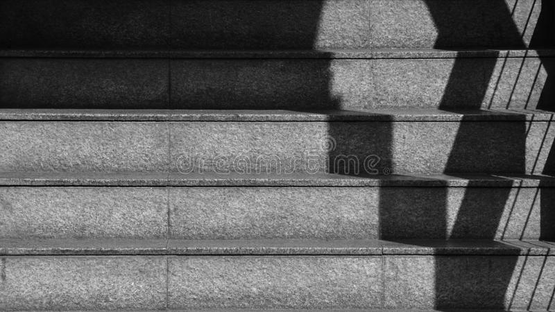 The shadow of the iron railing on the concrete stairs. - monochrome stock image