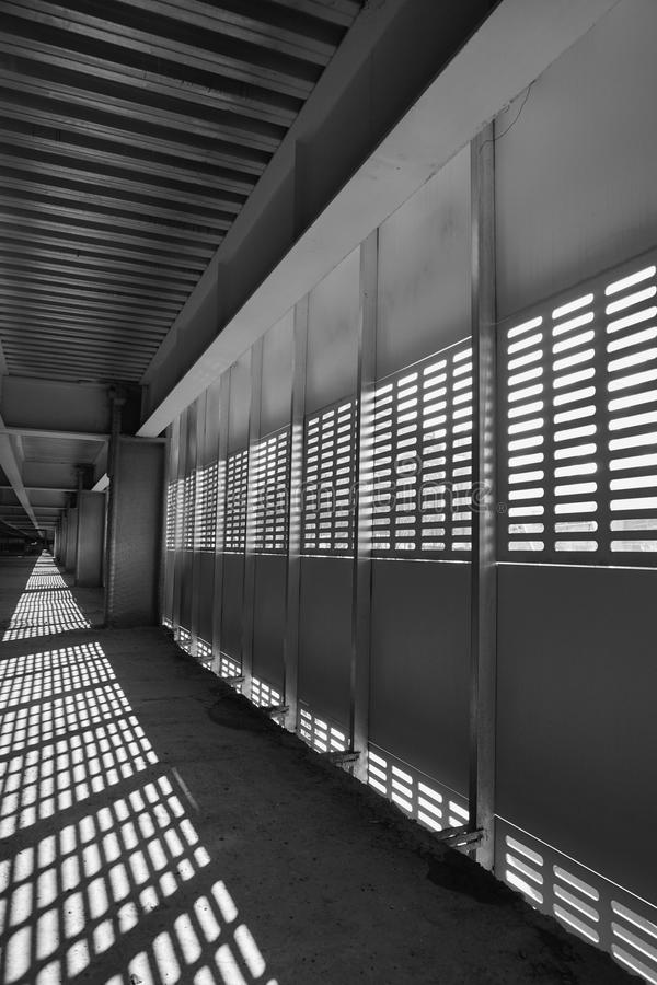 Shadow and light. Black and white. Sunny day light from metal lattice in abandoned unfinished shoping mall stock photography