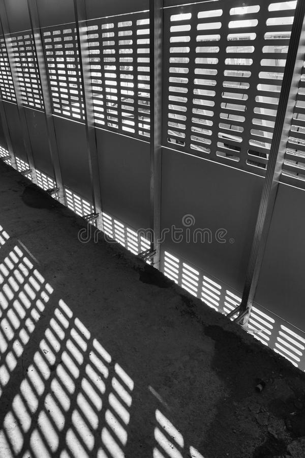 Shadow and light. Black and white. Sunny day light from metal lattice in abandoned unfinished shoping mall stock photos