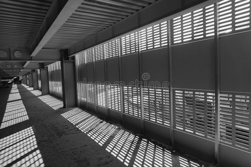 Shadow and light. Black and white. Sunny day light from metal lattice in abandoned unfinished shoping mall royalty free stock image