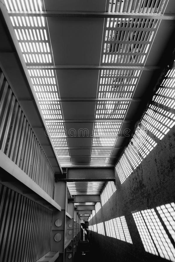 Shadow and light. Black and white. Sunny day light from metal lattice in abandoned unfinished shoping mall. Shadow and light. Black and white. Sunny light from royalty free stock images