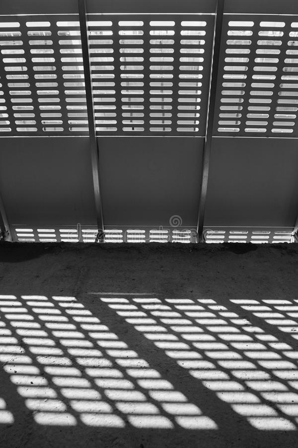 Shadow and light. Black and white. Sunny day light from metal lattice in abandoned unfinished shoping mall royalty free stock photography