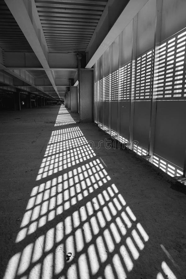 Shadow and light. Black and white. Sunny day light from metal lattice in abandoned unfinished shoping mall stock images