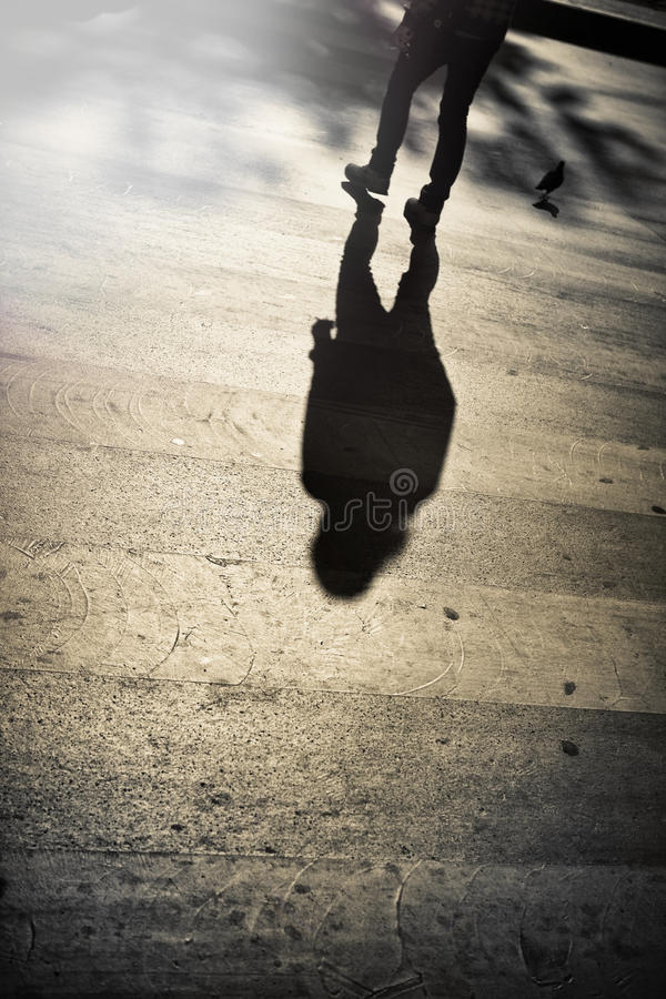 Shadow of a man crossing the street stock photography