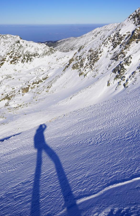 The shadow of a man doing winter trekking in the mountains royalty free stock photo