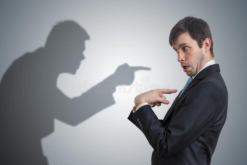 Shadow of man is pointing and blaming businessman. Conscience concept. Shadow of man is pointing and blaming businessman. Conscience concept stock image