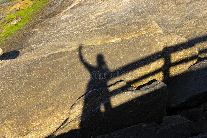 Shadow man with raised arm. Silhouette of Man Celebration Success Happiness on a stone sunset Background. stock images