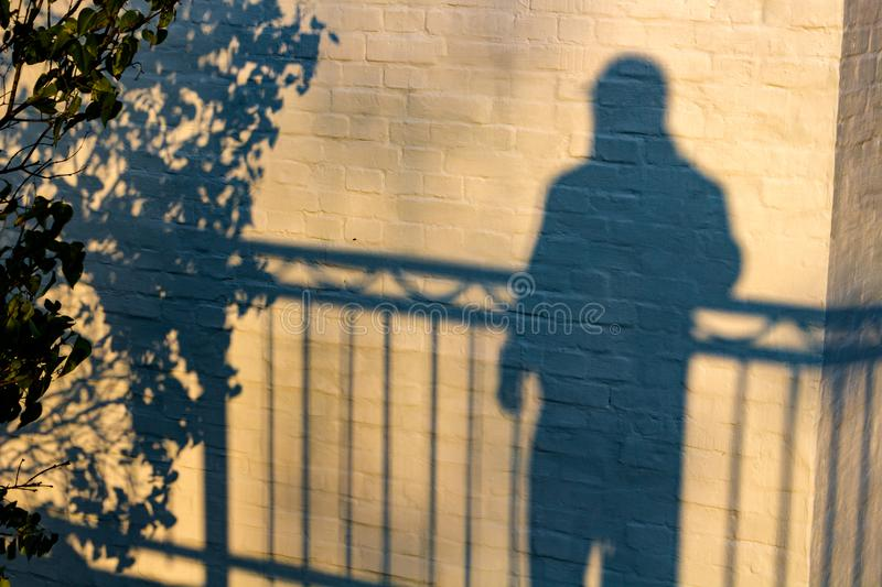 The shadow of a man on a white building wall. Background royalty free stock photo