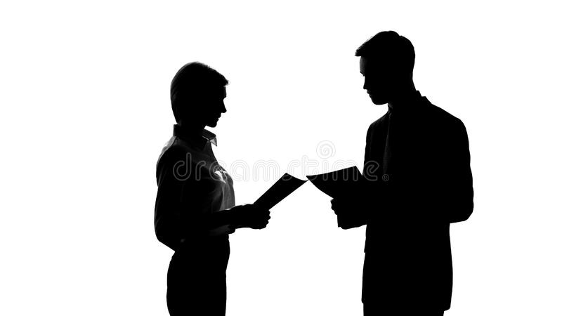 Shadow of man and woman discussing business project, holding documents, office royalty free stock image