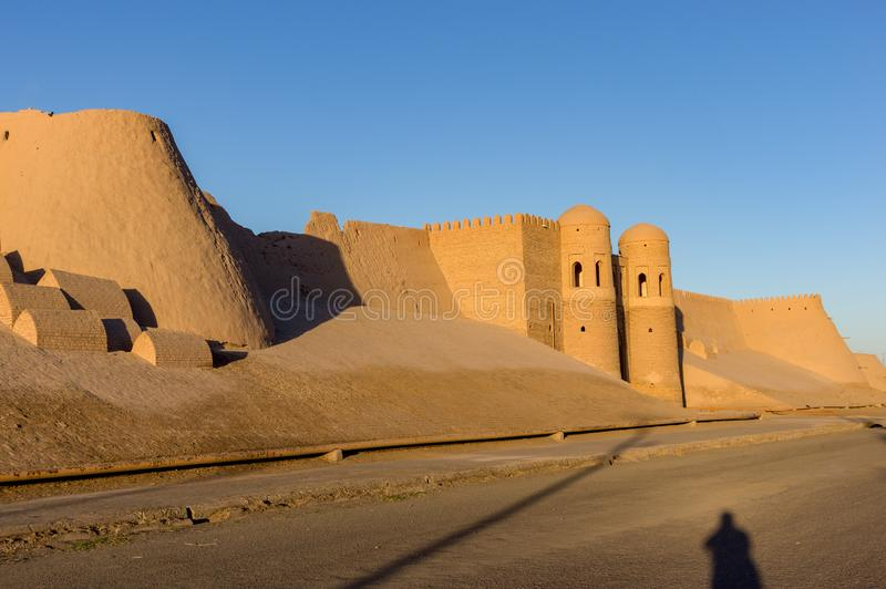 Khiva City Wall at sunset. Shadow of a photographer in front of Ichan Kala city wall and south gate during sunset - Khiva, Uzbekistan royalty free stock photos