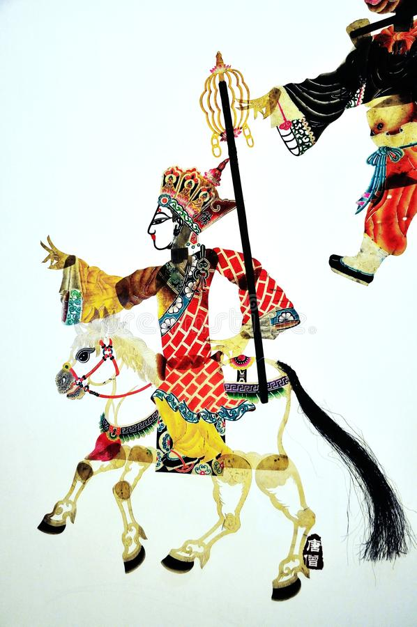 Shadow play about a monk riding a white horse royalty free stock images