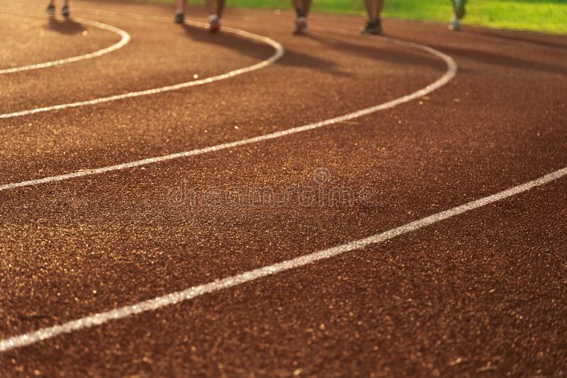 Shadow of running people exercise for health on the red and curve white line track floor of sport field in the morning sunrise stock photography