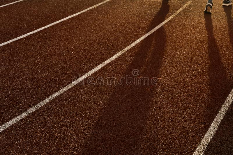 Shadow of running people for exercise on the red and white line track floor of sport field in the morning sunrise background stock images