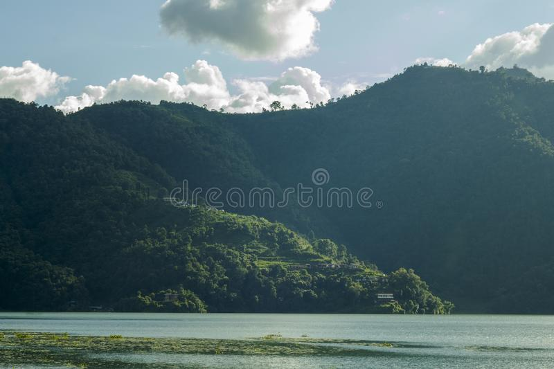 A shadow side of the mountain with green forest and houses under the blue sky with white clouds on the background of the lake stock photography