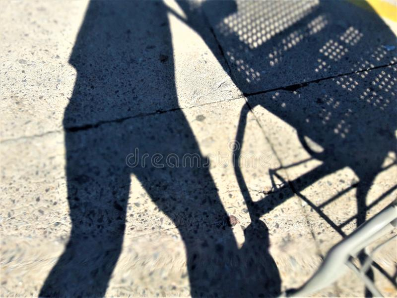 Shadow on the Sidewalk. Shadow of a shopper at a grocery store, clearly defined against the gray of the concrete. Crisp lines, interesting textures and colors royalty free stock photos