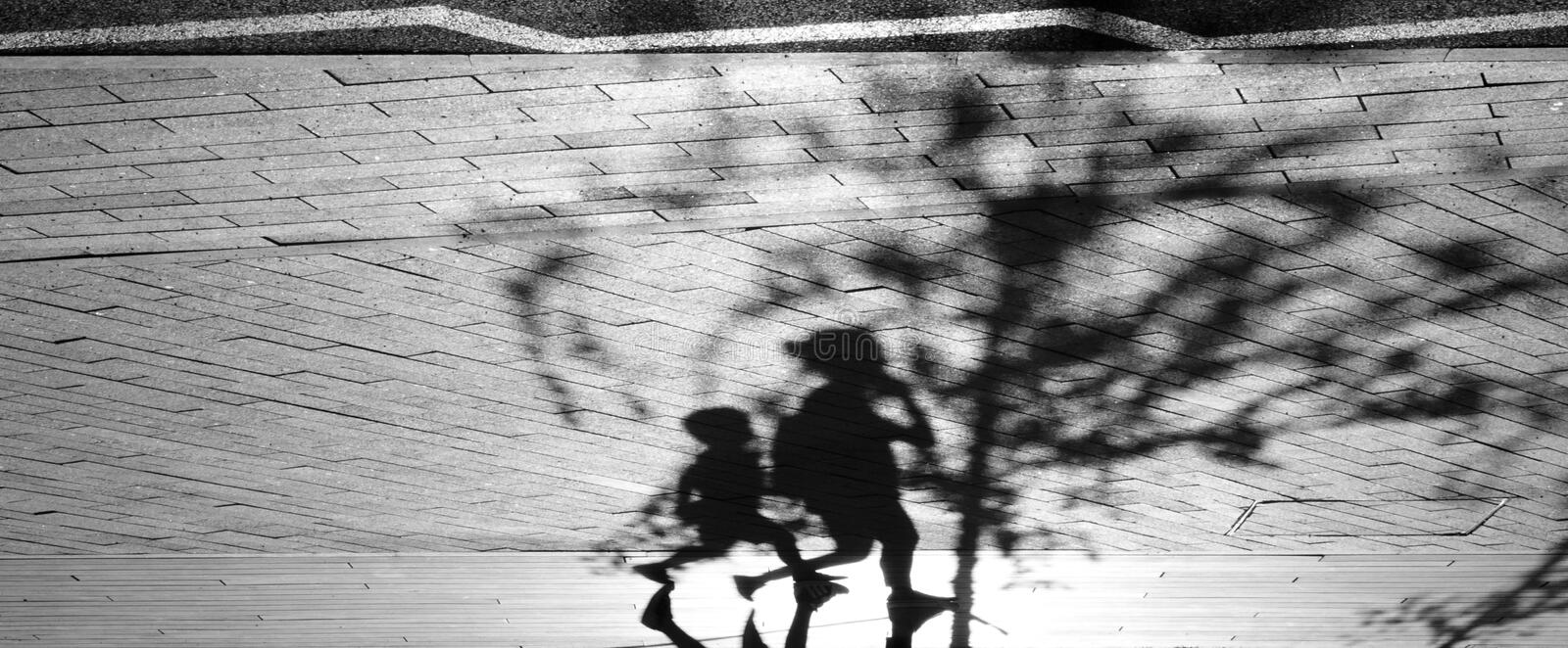 Shadow silhouette of two people walking royalty free stock image