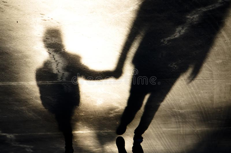 Shadow silhouettes of father and son walking hand in hand. Blurry vintage shadow silhouettes of father and son walking hand in hand in old asphalt road  in sepia royalty free stock image