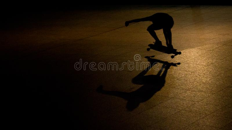 Skateboarder at night. Shadow of a skateboarder taken at night. Using spot light, I was able to shoot his elongated shadow royalty free stock image