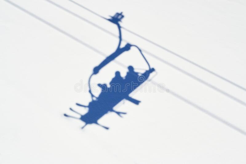 Shadow of skiers in a chairlift in Winter, high above a ski slope in Serre Chevalier ski domain, France, on a sunny day stock photo