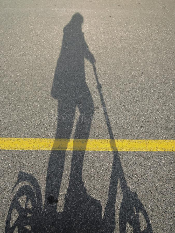 Shadow of a someone riding a scooter on a Sunny day on a bike path royalty free stock photos