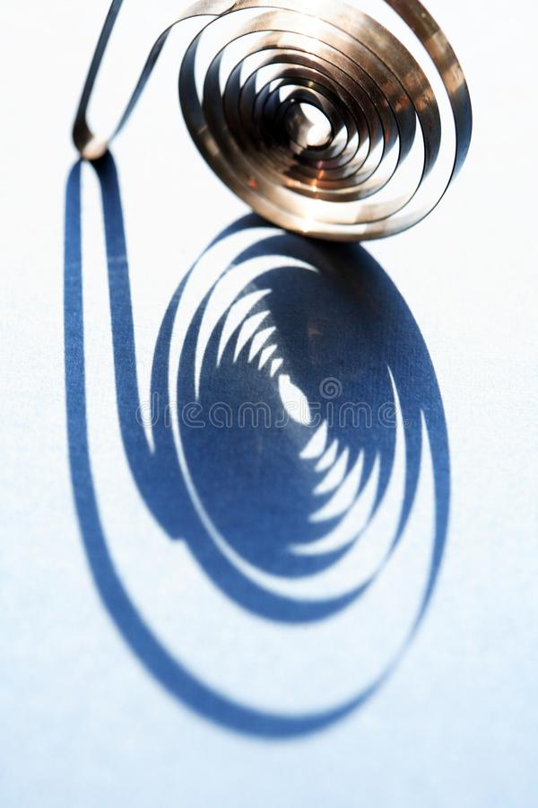 The Shadow Of Spiral. Industrial concept. Closeup of shadow of spiral on blue background stock images