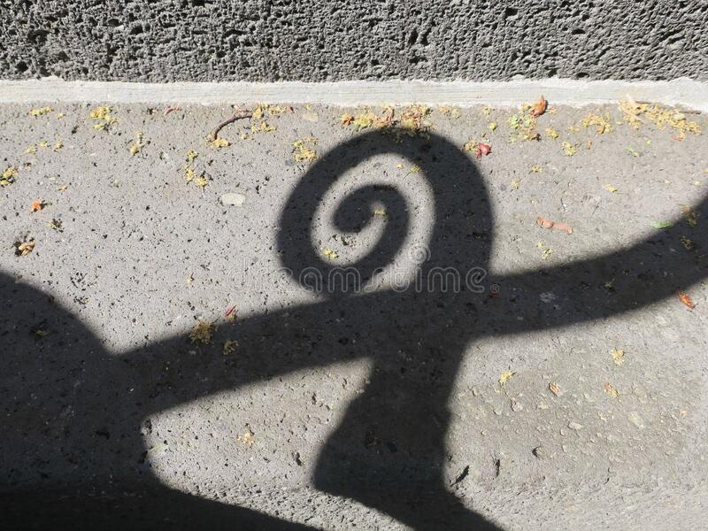 Shadow of a spiral, part of a handrail, on a stone wall stock photo
