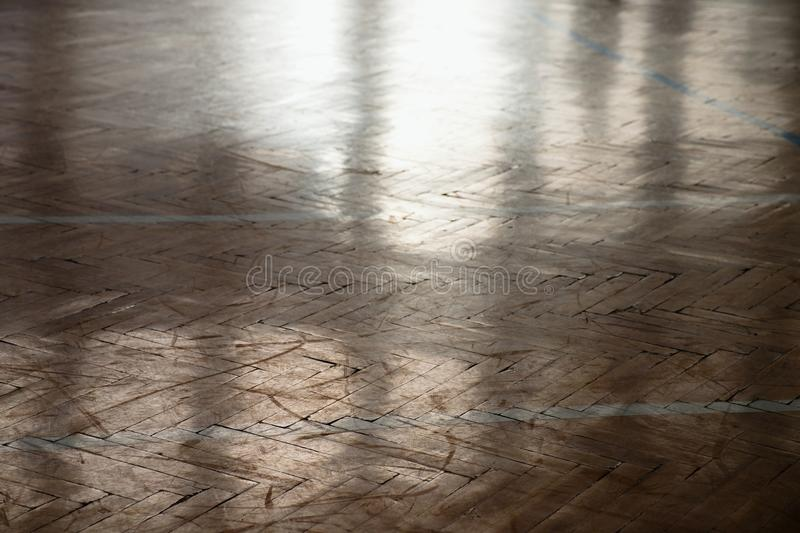 Shadow of sportsman. Window curtain wall reflecting in worn parquet floor at school gym. Shadow of sportsman. Window curtain wall reflecting in worn parquet royalty free stock photography