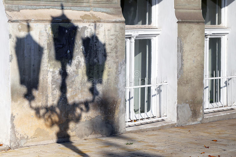 The Shadow Of A Street Lamp On The Wall Of An Old Dilapidated Ho Royalty Free Stock Photography