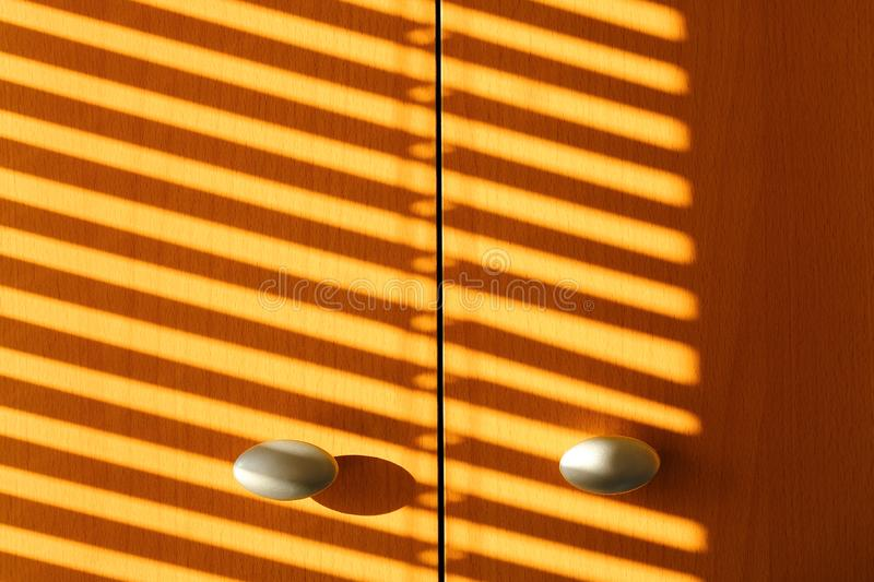 The shadow of the sun blinds on the doors of wardrobe.  royalty free stock images