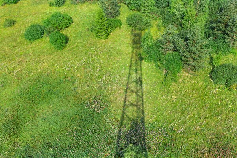 Shadow of telecommunication tower with radio antennas and satellite dishes on the green field with grass, bushes and stock image