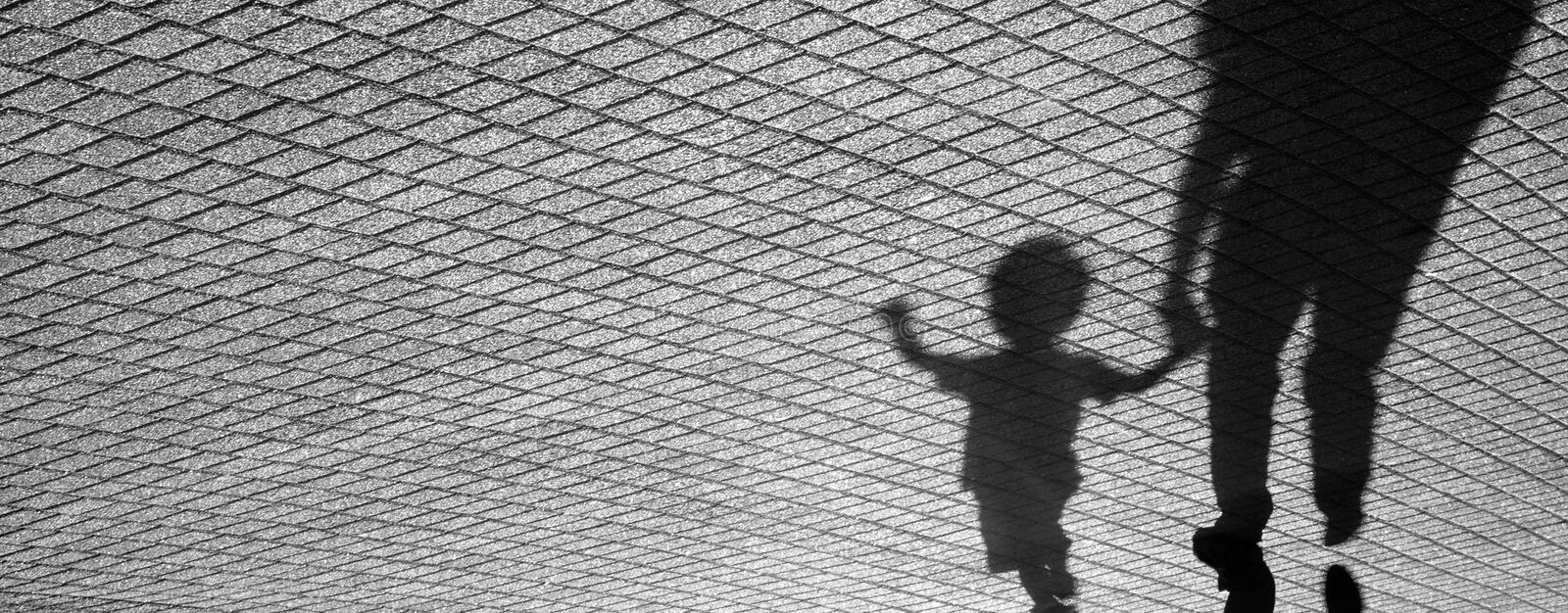 Shadow of a toddler and a man royalty free stock image