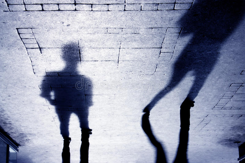 Shadow of two person on patterened sidewalk royalty free stock photos
