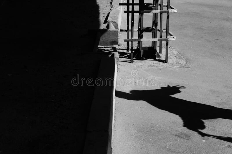 Shadow of a woman in a long jacket, with a handbag - with arms apart. On a bright spring day - a play of light from the rays of the sun, which cast a big shadow royalty free stock images