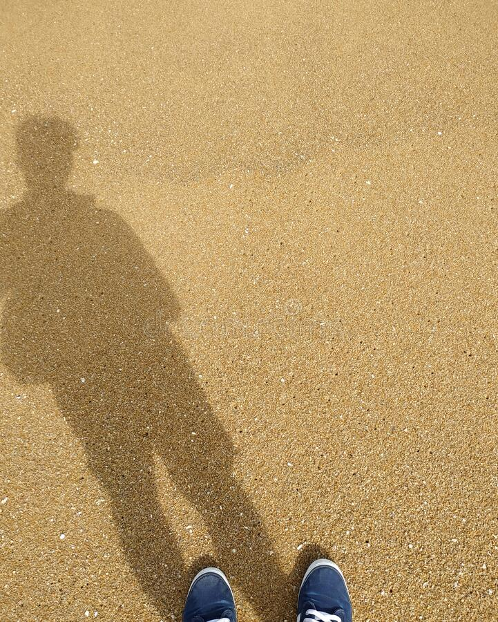 The shadow of a young man standing on the sand in holiday. royalty free stock image