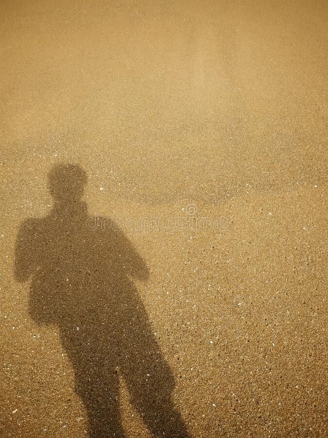 The shadow of a young man standing on the sand in holiday. royalty free stock photos