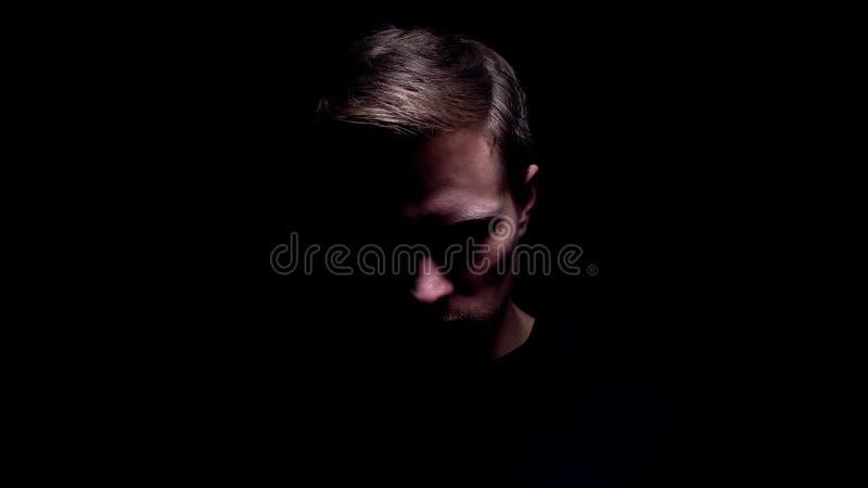Shadowed man looking down, maniac preparing for cruel murder, criminal. Stock photo royalty free stock photos