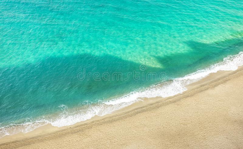Shadows of the beautiful Italian town of Tropea - Public beach and crystal clear sea water at sunrise royalty free stock image