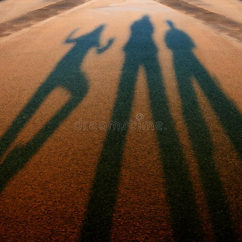 Shadows ending in the blurs. Long shadows from three persons at sunset on asphalt street ending in the blurs