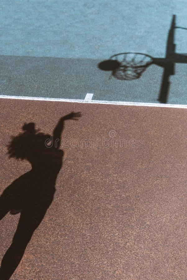 Shadows of female figure throwing ball into basket on ground of. Sports field stock photo