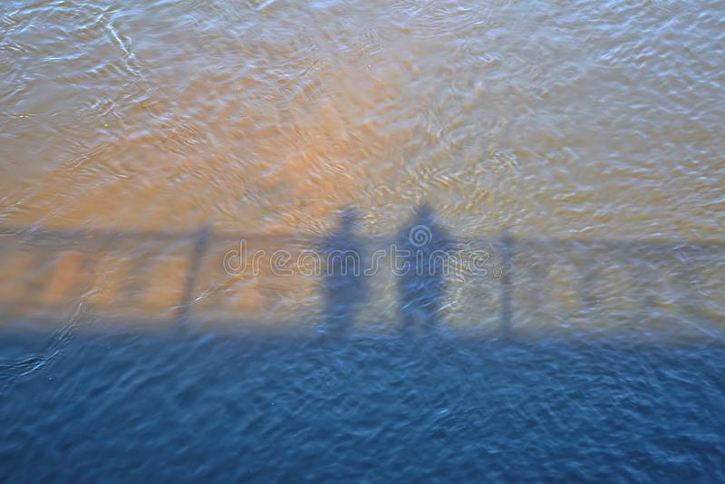Shadows of female and male silhouette on the surface of river water stock photo