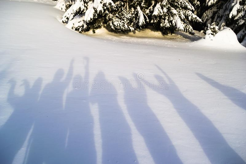 Shadows of hikers fooling around on a snow background. Simple, abstract, minimalist winter scene on a bright day royalty free stock image