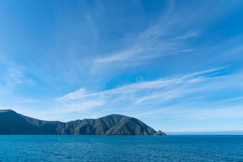 Shadows on hills under blue sky with light wispy cloud entering Queen Charlotte Sound stock photos