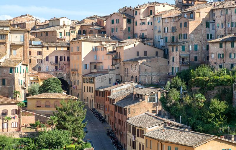 Shadows in Italian city with brick houses and towers of Siena, Tuscany. Tile roofs and brick structures in Italy.  royalty free stock photo