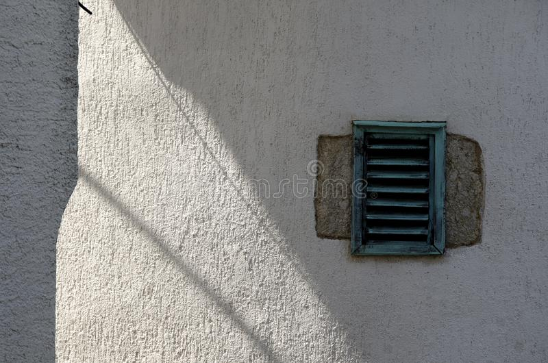Wall with vent. Shadows on an old plastered wall with a small vent stock images