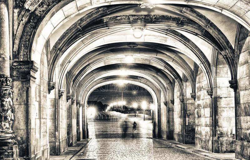 Shadows of people walking at night under ancient medieval loggia stock images