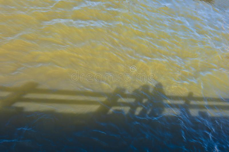 Abstract shadows reflect off of ripply river water. Minimalist image of shadows reflecting in waters below a pier on the Columbia River Gorge royalty free stock image