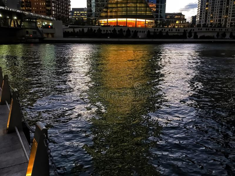 Chicago riverwalk and glimmering lights on water as the sun sets, casting shadows royalty free stock photos