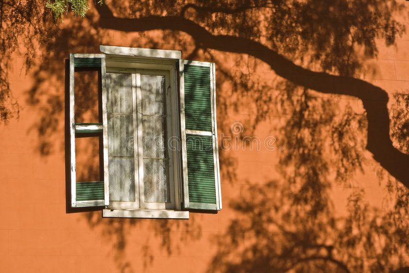 Shadows of Summer. A window with lace curtains and green shutters on a tan stucco wall with a large tree shadow covering the wall royalty free stock photography