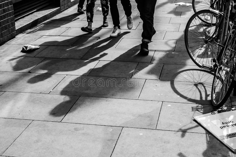 Shadows of three walking pedestrians projected on the sidewalk. With bycicle on the side stock images