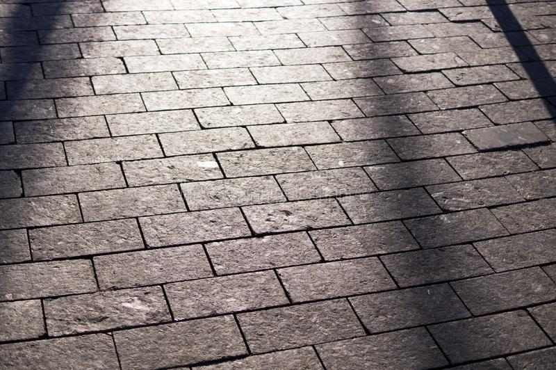 Shadows on the tile paved sidewalk with perspective. background, lighting. Sun shadows on the tile paved sidewalk with perspective. background, lighting royalty free stock photos